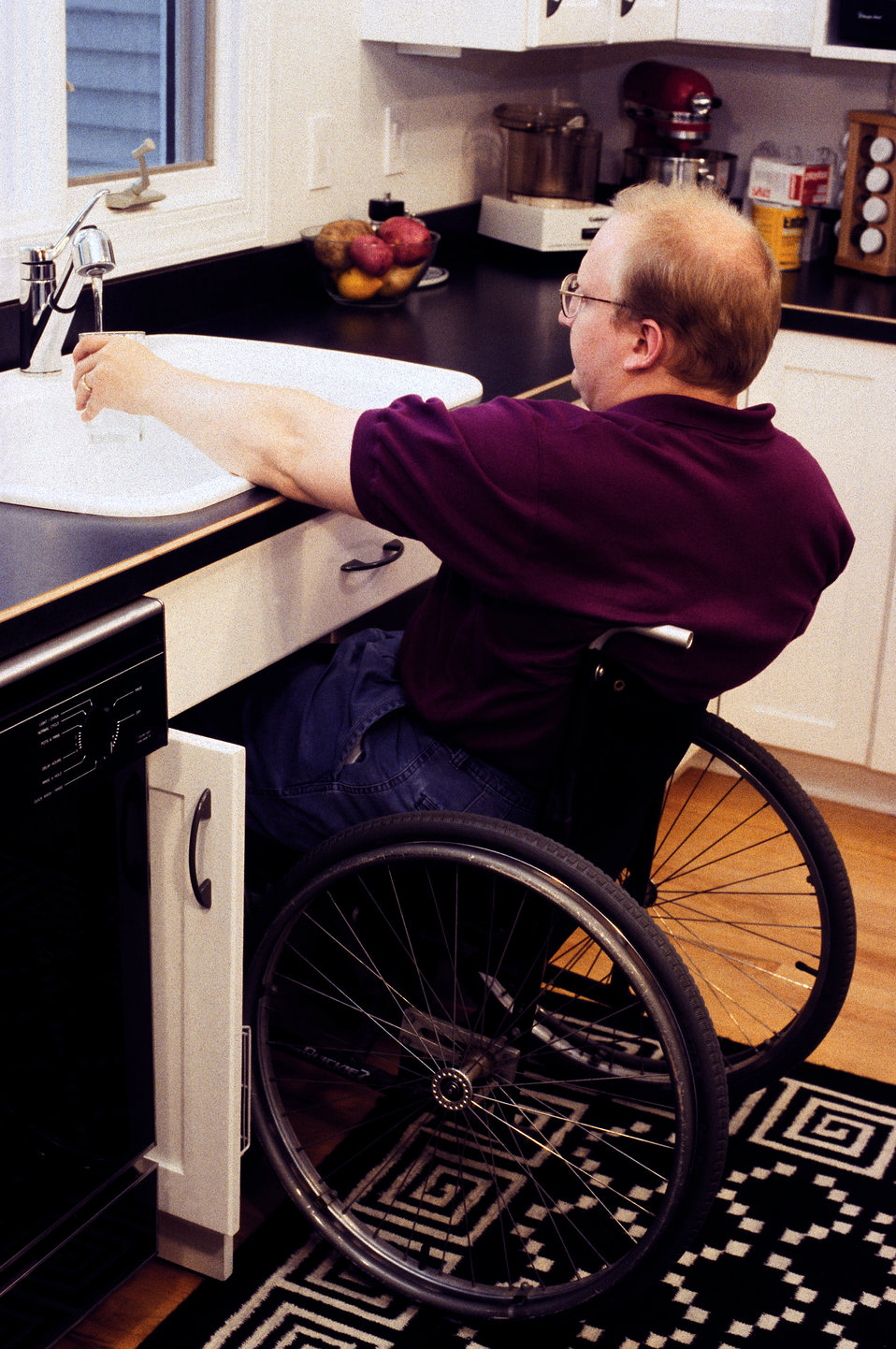 This man seated in his wheelchair, was in a customized kitchen outfitted with adaptable cabinetry, which allowed him to pull his seat closel