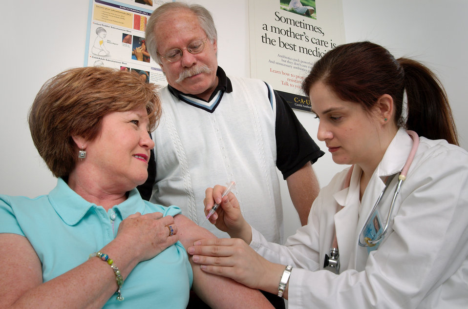 In this 2006 photograph, a middle-aged woman was receiving an intramuscular vaccination into her left shoulder muscle from a female nurse. A