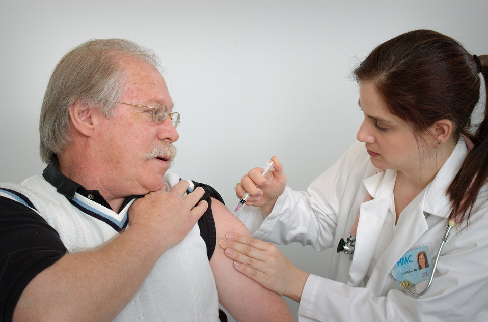 Photographed here in this 2006 image, was a middle-aged man receiving an intramuscular immunization into his left shoulder muscle from a fem