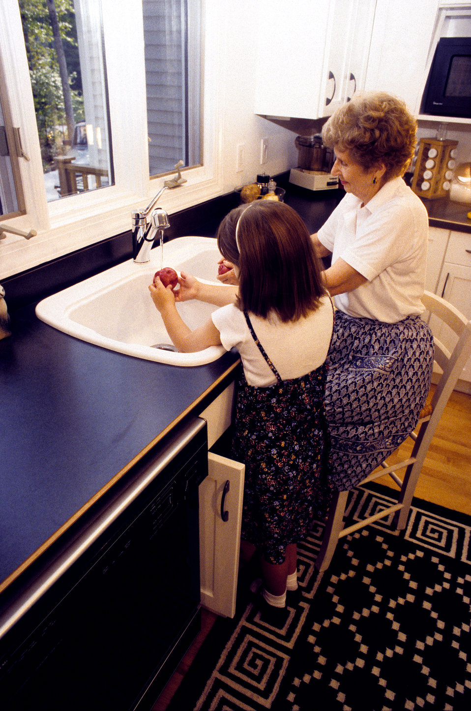 : This grandmother and her granddaughter were in a customized kitchen outfitted with adaptable cabinetry, which allowed the elderly woman to