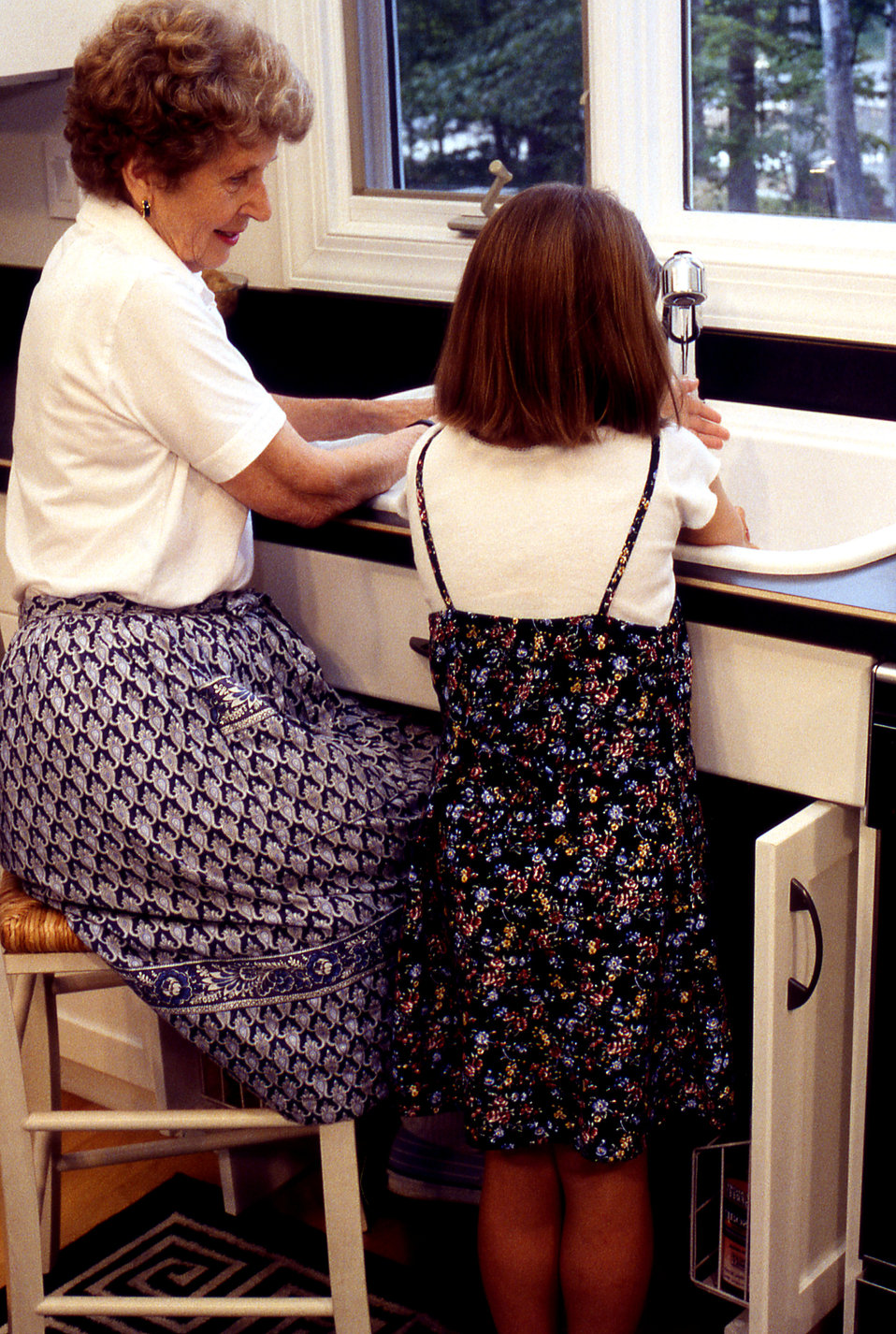 This grandmother and her granddaughter were in a customized kitchen outfitted with adaptable cabinetry, which allowed the elderly woman to p