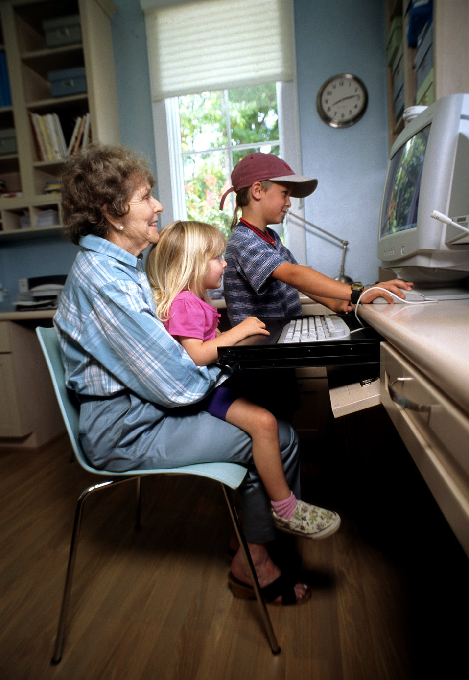 This 2000 image depicted an elderly woman seated at a home computer workstation, while her two grandchildren, a young girl and boy play on t