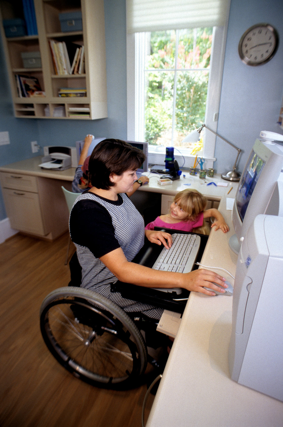 This 2000 image depicted a wheelchair-seated woman seated at her home computer workstation, while two children, a young girl and boy, were p