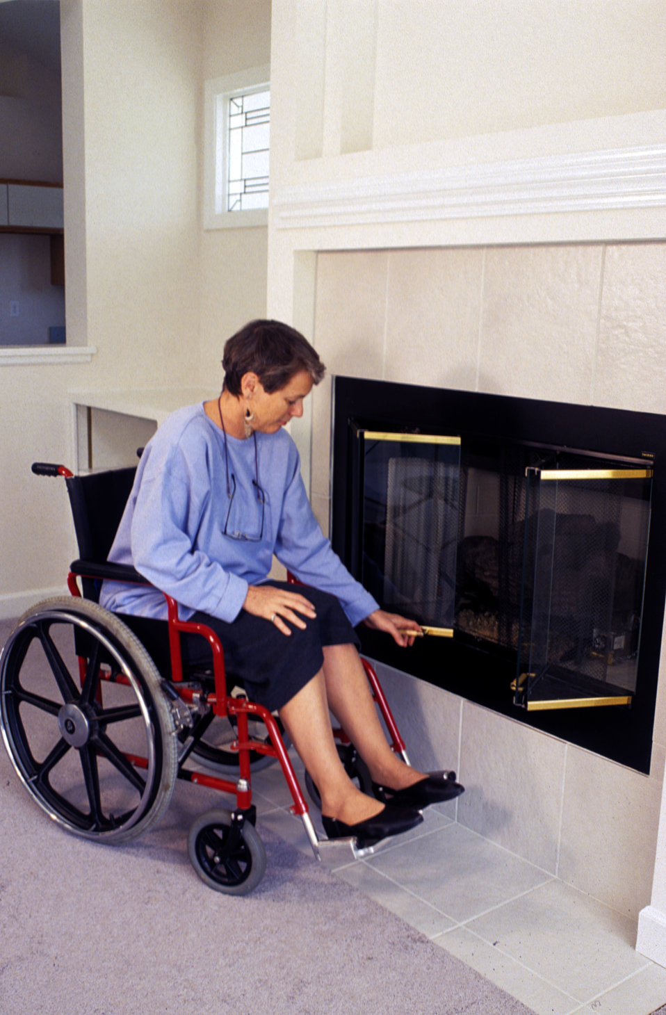 This 1994 image depicted a woman who was seated in a wheelchair in front of a raised hearth-type fireplace as she was opening the fireplace