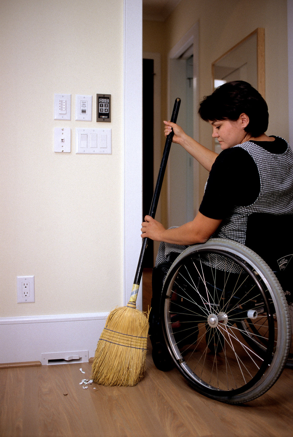 With broom in hand, this 2000 photograph showed a wheelchair-seated woman as she was sweeping some debris towards a floor level intake vent
