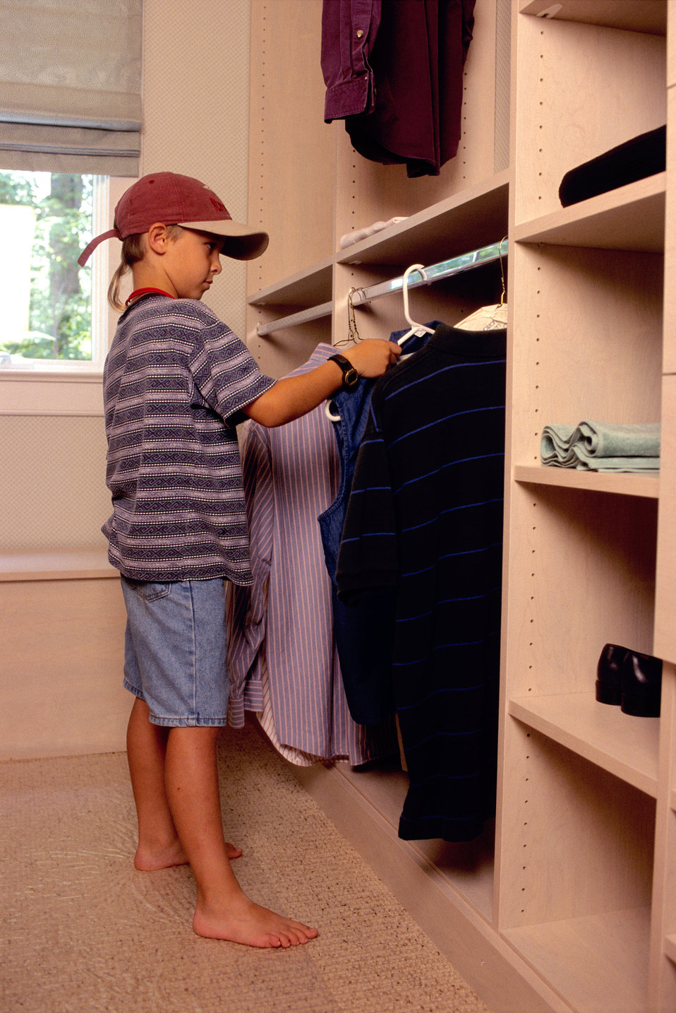 The young boy depicted in this 2000 image was shown either hanging, or removing a shirted clothes hanger, while standing on the carpeted flo
