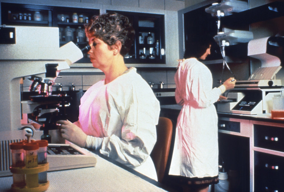 This photograph shows researchers at work in a CDC laboratory identifying the cause of an infectious disease outbreak.