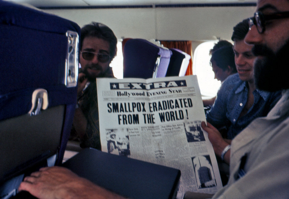 These individuals on an airplane were admiring a newspaper article entitled 'Smallpox Eradicated from the World!'