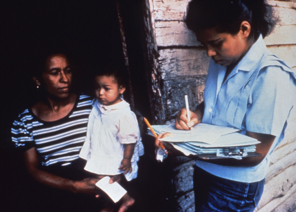 This photograph shows a CDC, Public Health Advisor (PHA) interviewing a resident of a disease stricken community.