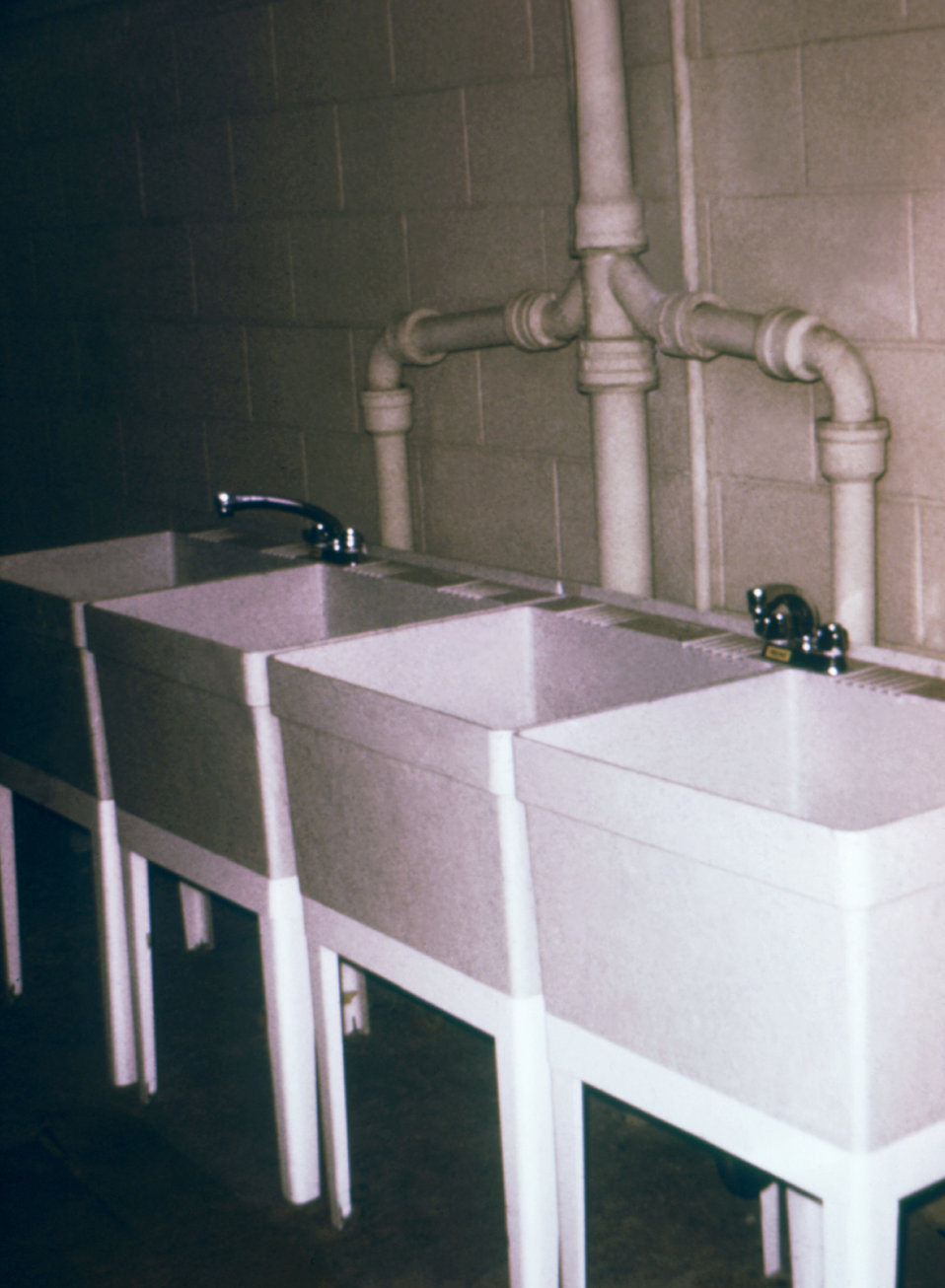 These laundry tubs are an example of proper water supply conditions because the faucets are placed above the water spill rims.