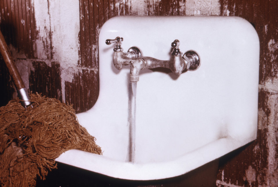 The placement of the water faucet above the water spill rim of this mop sink is an example of proper sanitary practice.