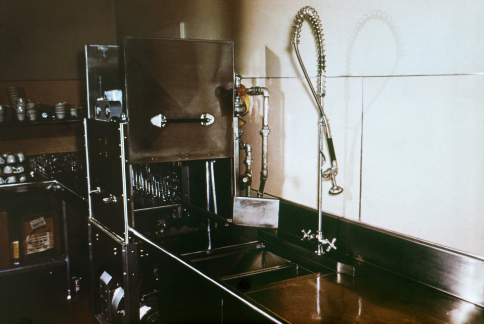 This photograph shows the proper installation of a manual pre-rinse sprayer on a dishwashing machine above its water spill rim.