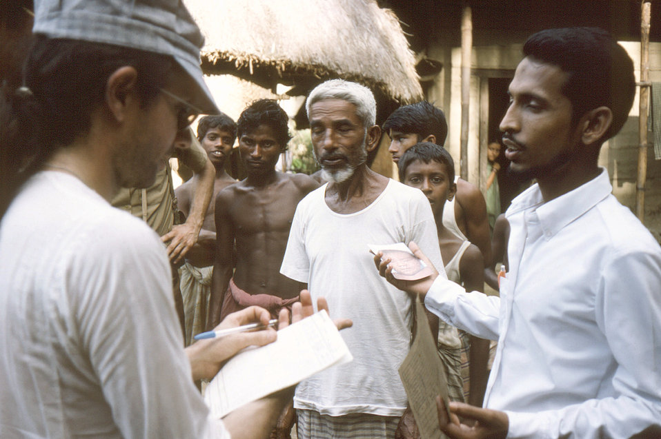Photographed in the Sylet District of north-eastern Bangladesh, wearing a cap, was Dr. Michael Schwartz, along with his translator as they w