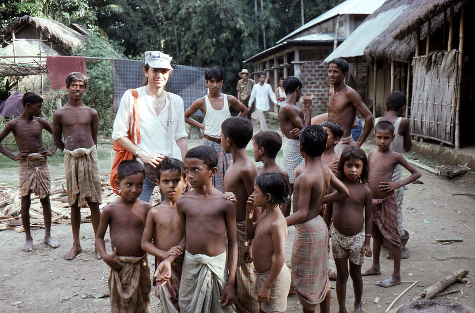 Photographed in the Sylet District of north-eastern Bangladesh, wearing a cap, was Dr. Michael Schwartz, as he was in the process of conduct
