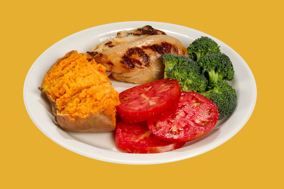 This white ceramic plate had been topped with a healthy, balanced meal consisting of a broiled chicken breast, half a sweet potato, three sl