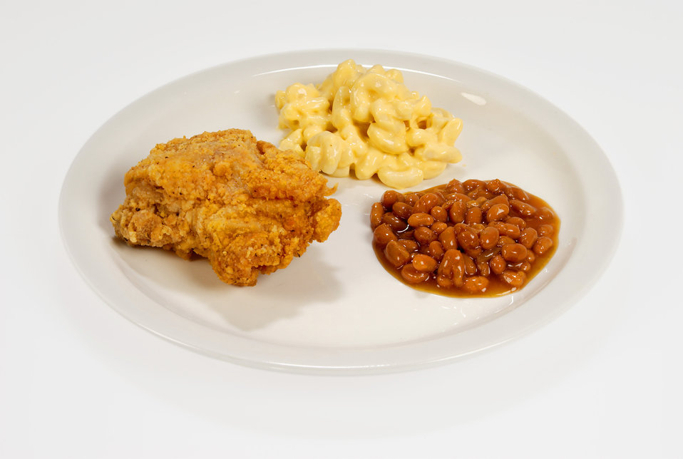 This white ceramic plate had been topped with some rather high caloric foods including a fried chicken breast, a serving of macaroni and che