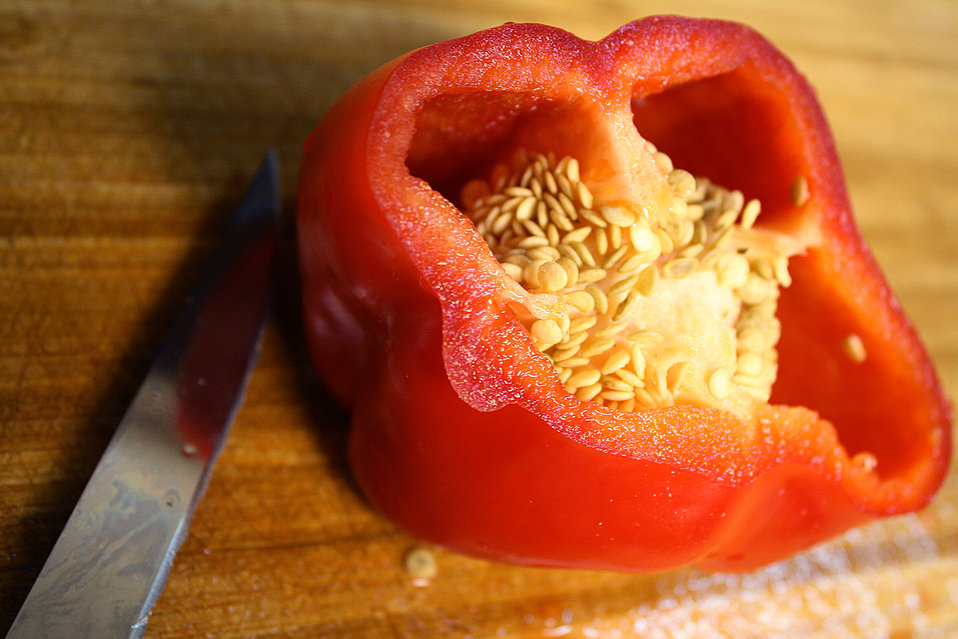 This picture was taken inside a home kitchen, and depicts a halved red bell pepper, Capsicum annuum, set atop a clean, well-worn cutting boa