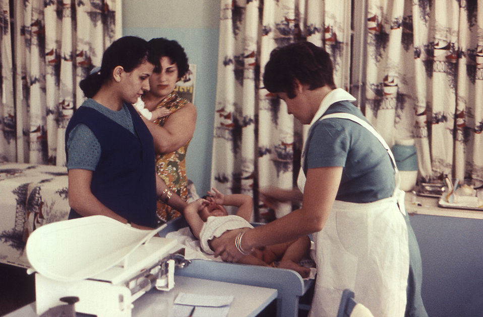 This 1969 image depicted two mothers who were seeking the assistance of a nurse inside an Israeli Well-Baby clinic. At this point in the vis