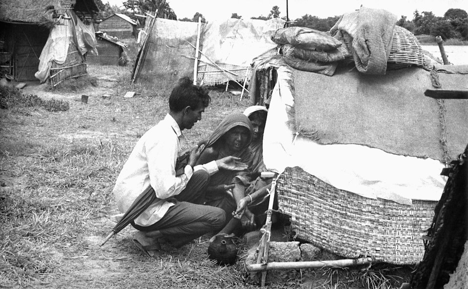 This 1975 photograph depicted a volunteer smallpox eradication team participant examining the smallpox vaccination sites on the family membe