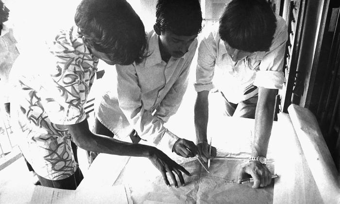 This 1975 photograph depicted a number of smallpox eradication team members huddled around a village 'infection map', which reflected the ge