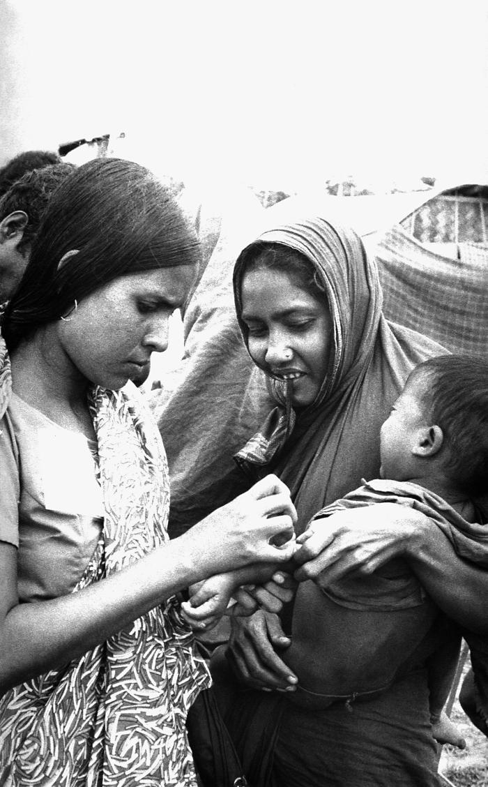 This 1975 photograph depicted this volunteer smallpox eradication team vaccinator while in the process of vaccinating a young woman's child