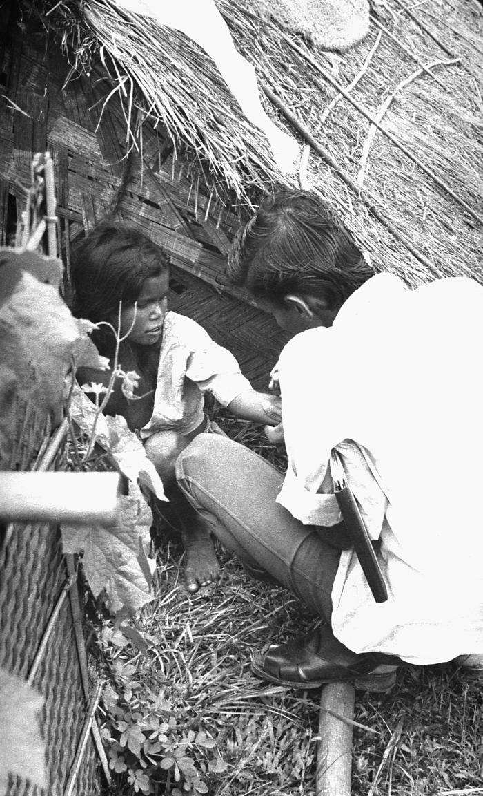 This volunteer smallpox eradication team vaccinator was in the process of vaccinating to a girl who at the time, was living with her family