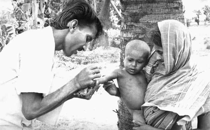 This volunteer smallpox eradication team vaccinator was in the process of administering a vaccine to a young child as his mother held him st