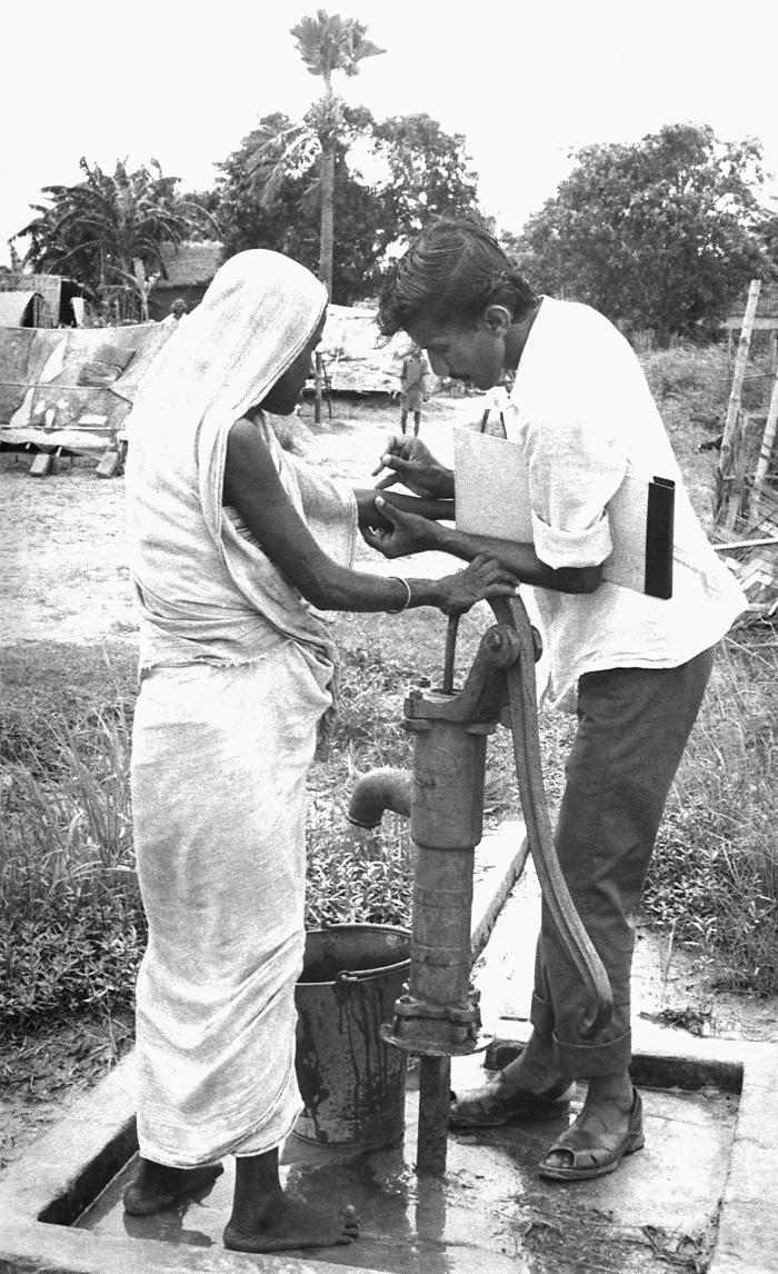This volunteer smallpox eradication team vaccinator was in the process of administering a vaccine to a woman who was obtaining water from a