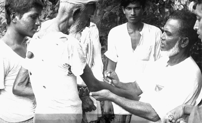 'The saintly' Mr. Rahman, a man from the town of Noakhali, was photographed here while he was demonstrating the method by which a smallpox v