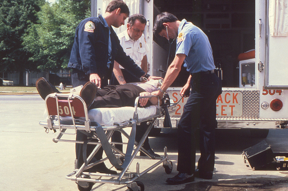 Here we see three emergency medical service (EMS) workers who'd arrived in an ambulance to a scenario involving a man who'd collapsed, and w
