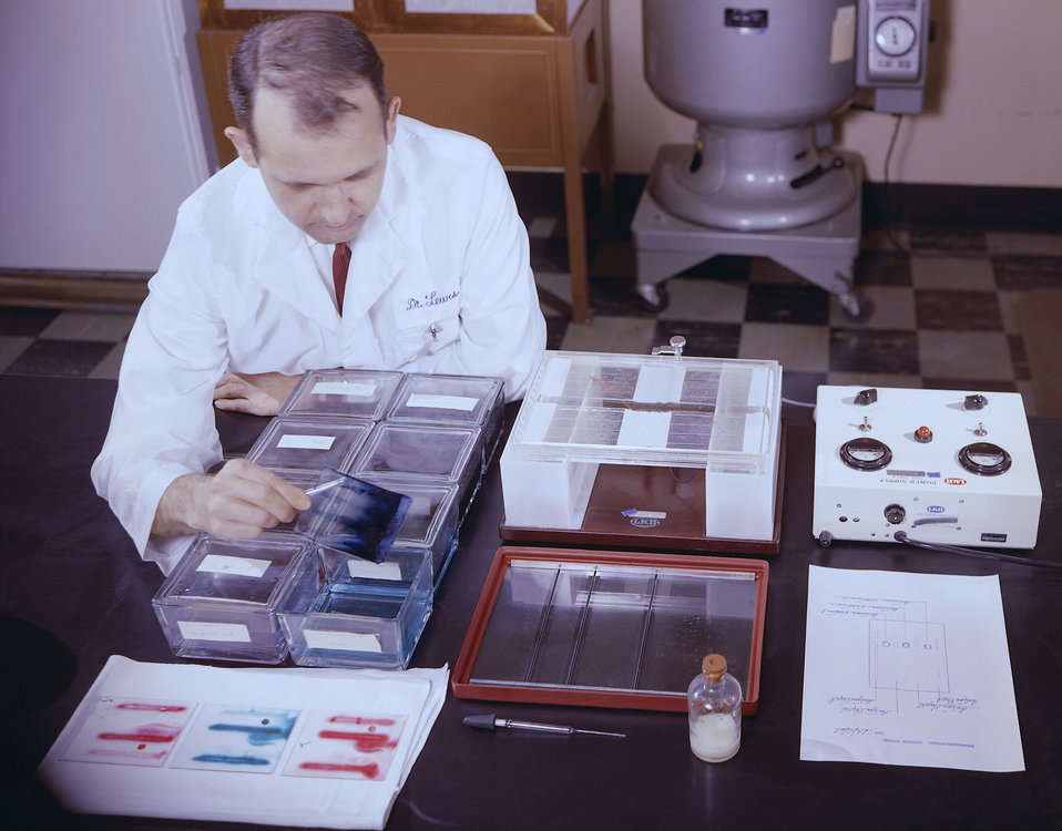 This historic 1963 photograph depicted laboratorian, Dr. V.J. Lewis, as he was seated in his lab analyzing the results produced by an immuno
