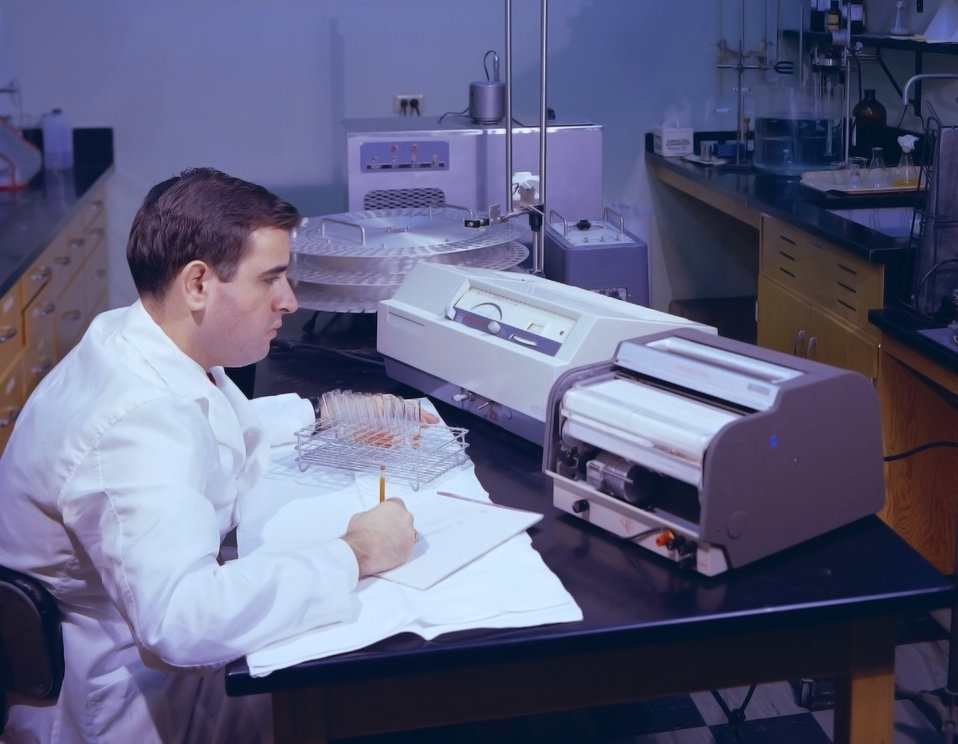 This historic 1963 photograph depicted Dr. Schulbind, as he was performing a streptolysin determination study, by measuring sample levels of