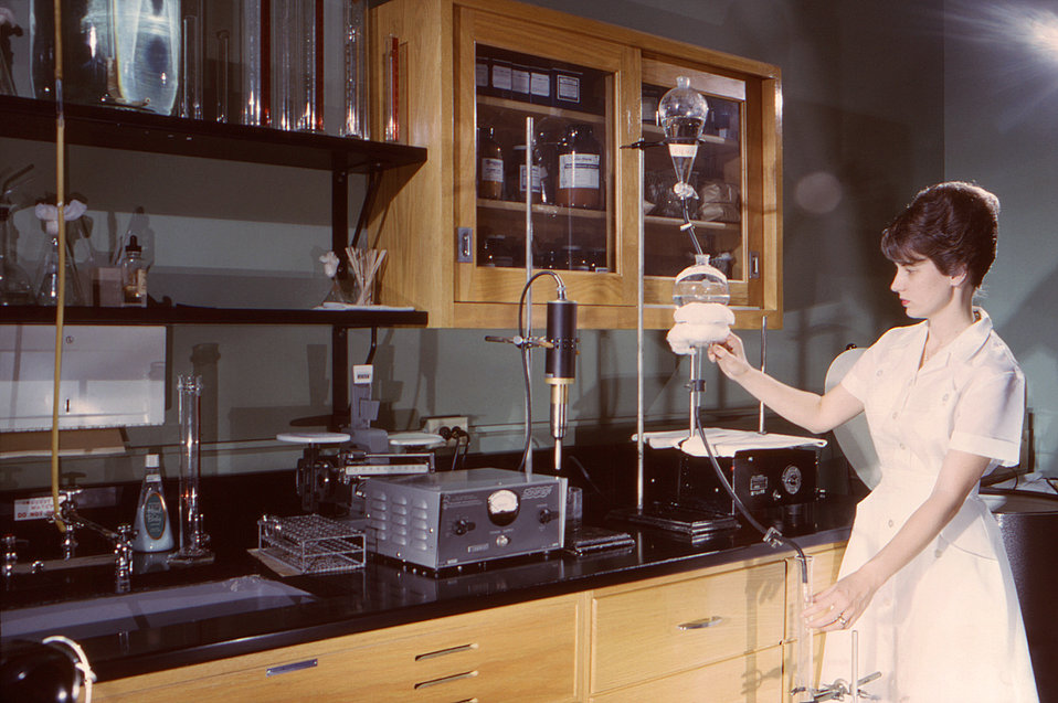 This historic 1963 photograph depicted a lab technician, Geraldine Wiggins, as she was performing a chromatographic antigen fractionation, w