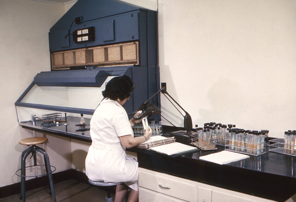 This historic 1962 photograph depicted a technician as she was seated in her mycobacterial laboratory, examining an unknown mycobacterial cu