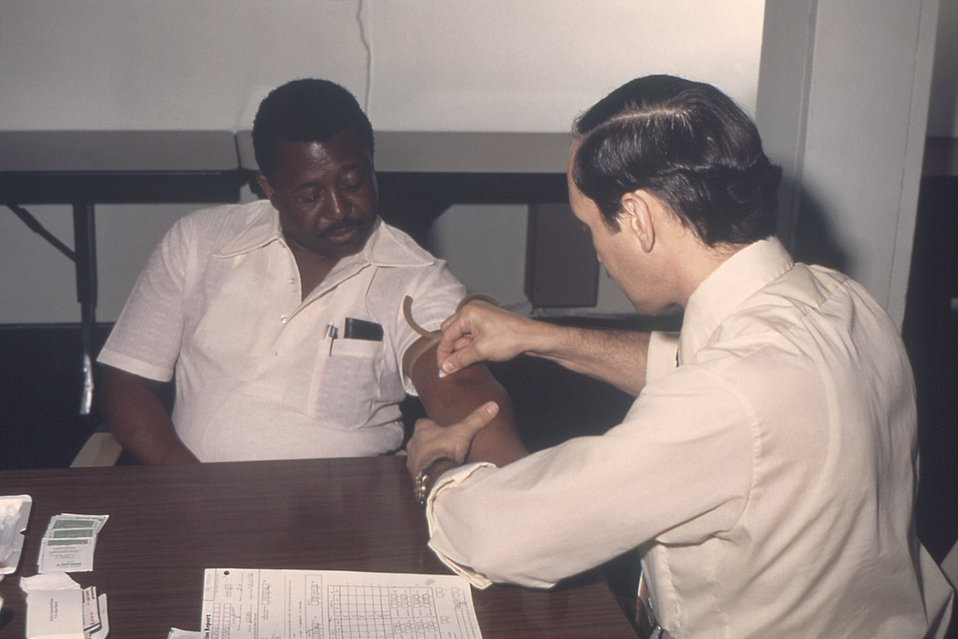 From 1976, this photograph depicted Dr. Gary Noble as he was preparing to draw blood from a male patient that would be tested for its concen