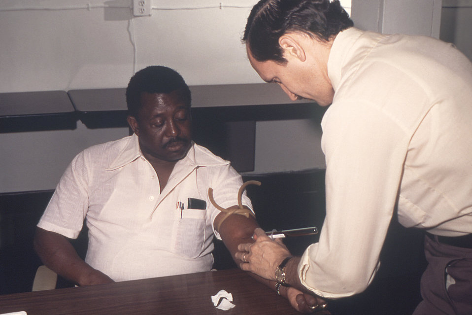 From 1976, this photograph depicted Dr. Gary Noble as he was drawing blood from a male patient that would be tested for its concentration of