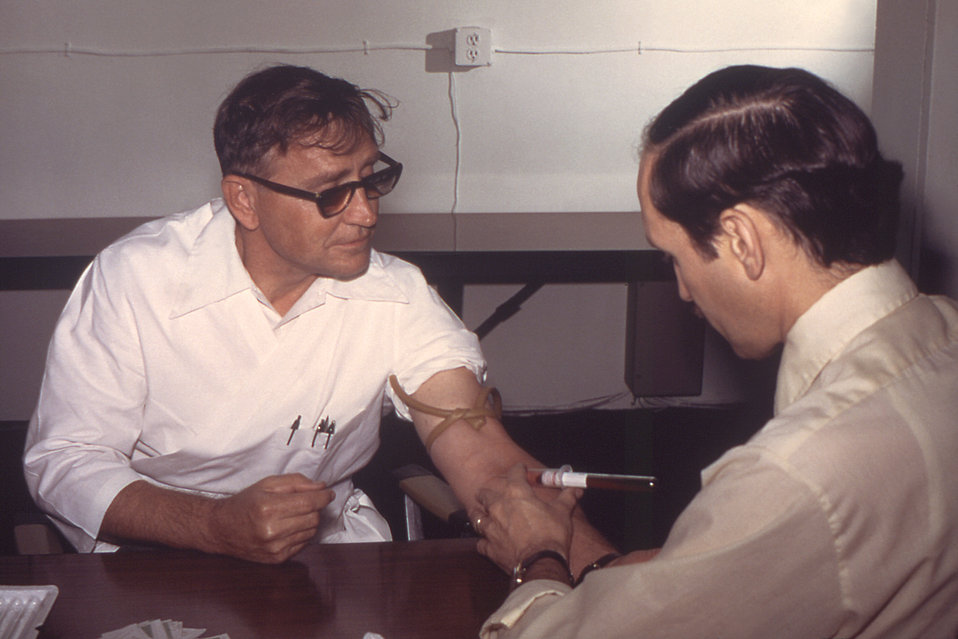 From 1976, this photograph depicted Dr. Gary Noble as he was in the process of drawing blood from a male patient that would be tested for it