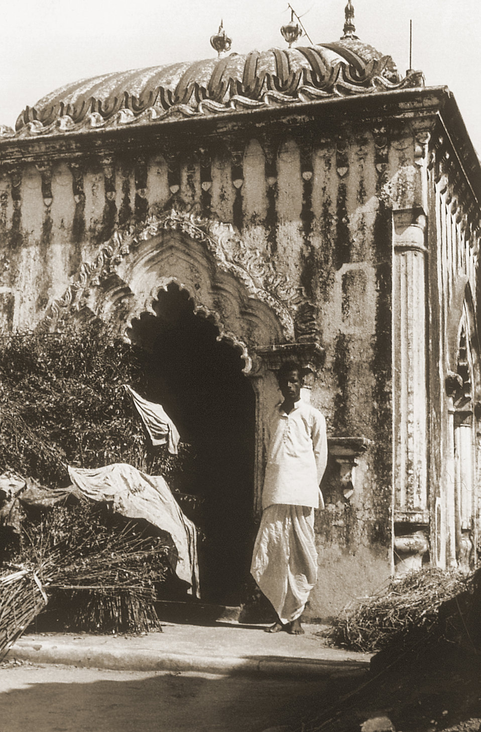 Standing outside the edifice, this 1975 image depicts the son of Pawapuri, or Pava, homeowner, who'd built a small temple in the name of his
