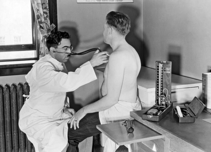 This historic 1932 photograph showed a physician conducting a medical examination of a dairy worker at the state tuberculosis sanatorium in