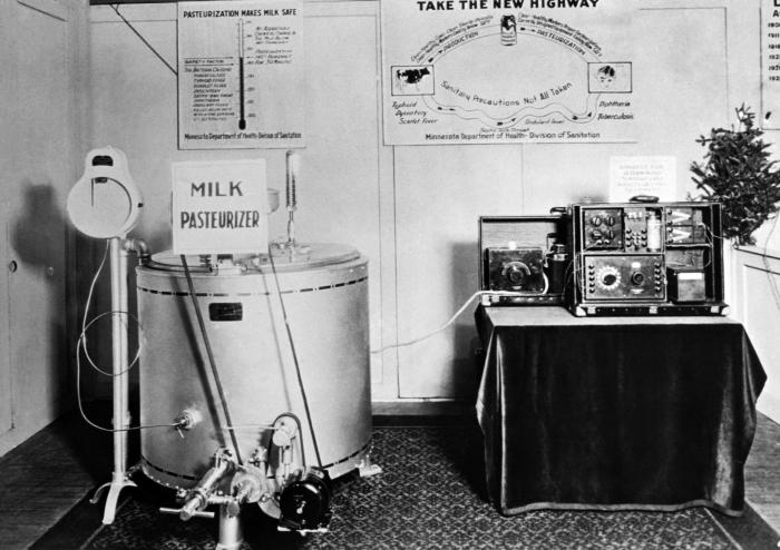 This historic photograph depicted a milk pasteurizer and thermocouple exhibit at the 1929 Minnesota State Fair. On the left side, back wall,