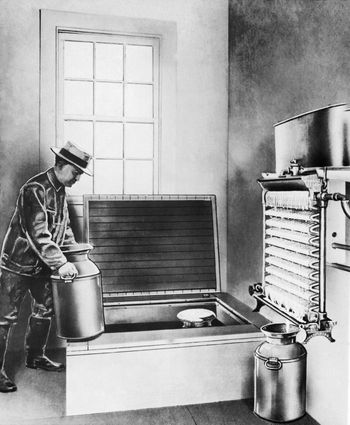 This heavily photo-retouched historic 1929 image depicted a dairy worker as he was placing cans of cooled milk into a cold storage tank. Hea