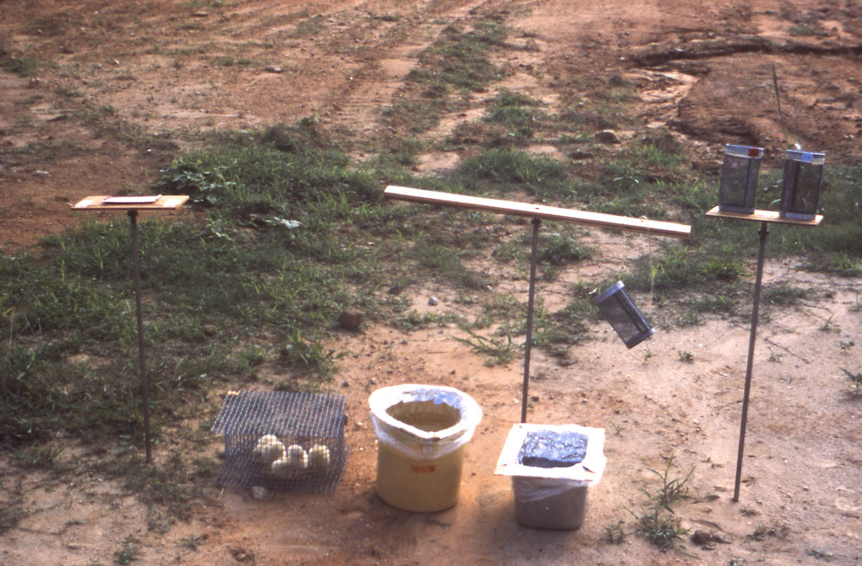 This image depicts a number of apparatuses set up in a field in order to conduct bioassay studies and measure ultra-low volume (ULV) aerosol