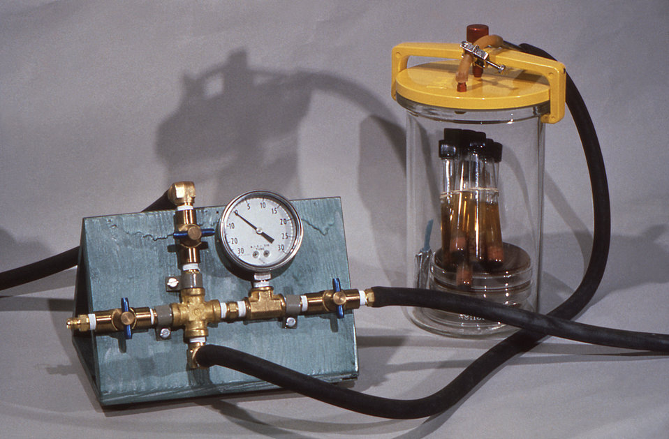 This 1975 image depicts a laboratory apparatus still life that included an air-tight, yellow-topped Gas-Pak jar containing tubes and Petri d