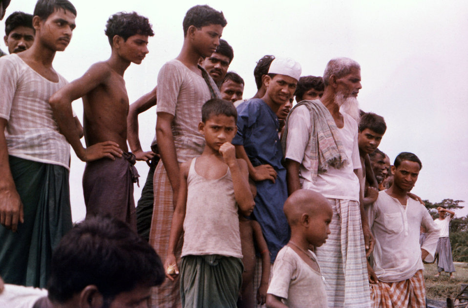 Depicted in this September, 1975 photograph, was a grouping of Bangladeshi villagers, amongst whom, stood the white-bearded father of a woma