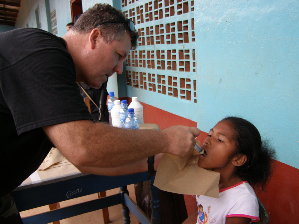 This image depicts Lt. Cmdr. Gary Brunette as he was in the process of administrating medicine to a young patient at a remote clinic in Nica