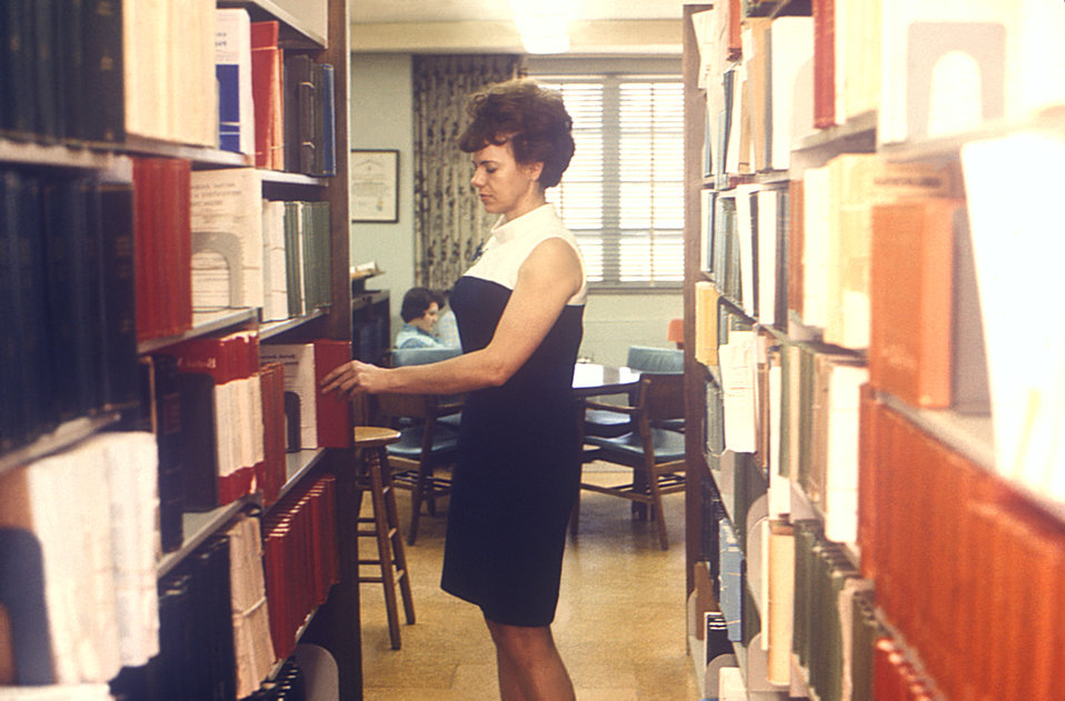 This 1970 photograph depicts librarian, Evelyne Coggins, as she was organizing shelved library books in the Centers for Disease Control and