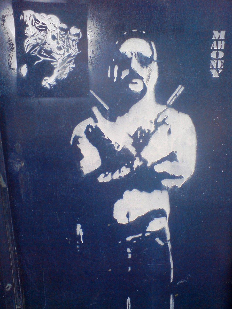 'Man with guns' graffiti, reproducing the poster of Australian movie Chopper with Eric Bana.