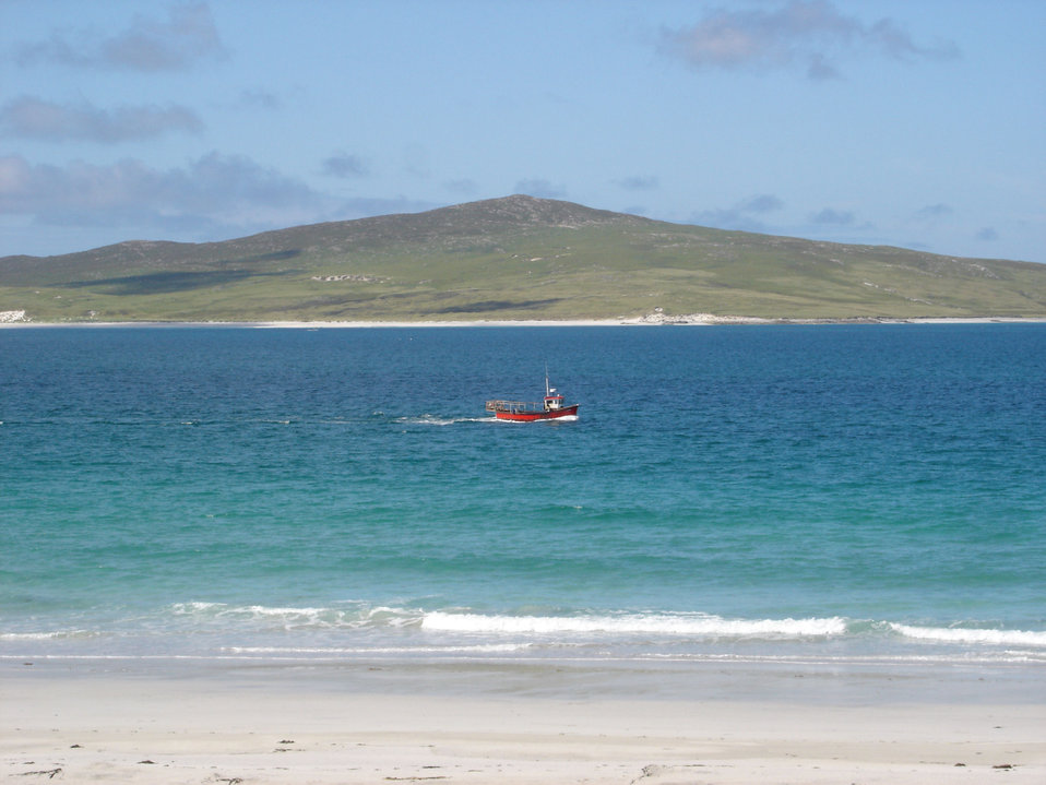 A Berneray fishing boat passes the west beach. In the centre distance is Pabbay, an unpopulated island in the Sound of Harris.