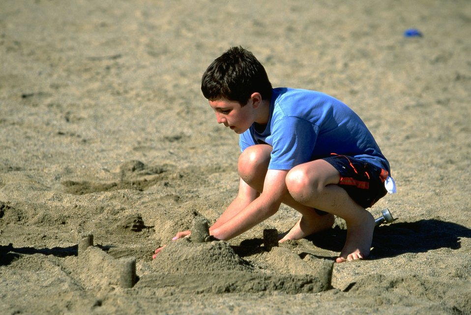 Boy building sand castles in the sand on the beach of Hauser Lake