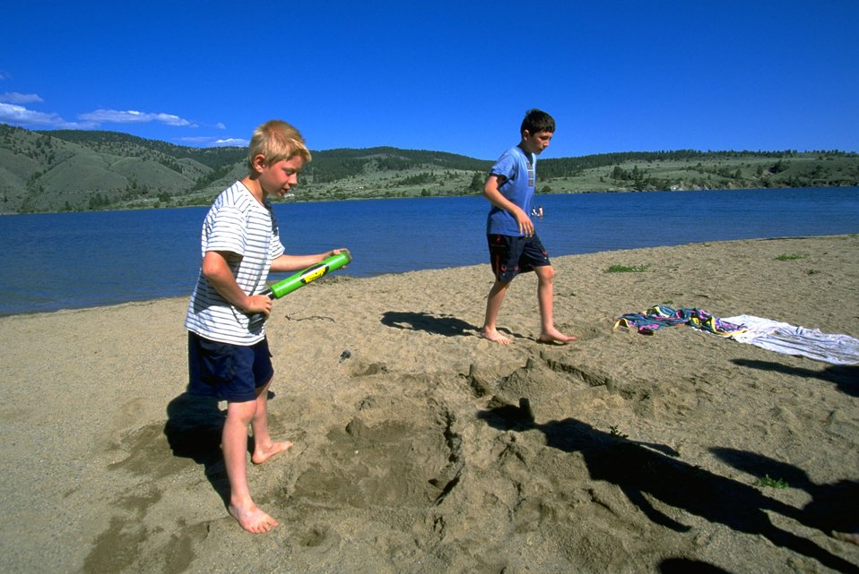 Boys playing on the sandy beach at Hauser Lake